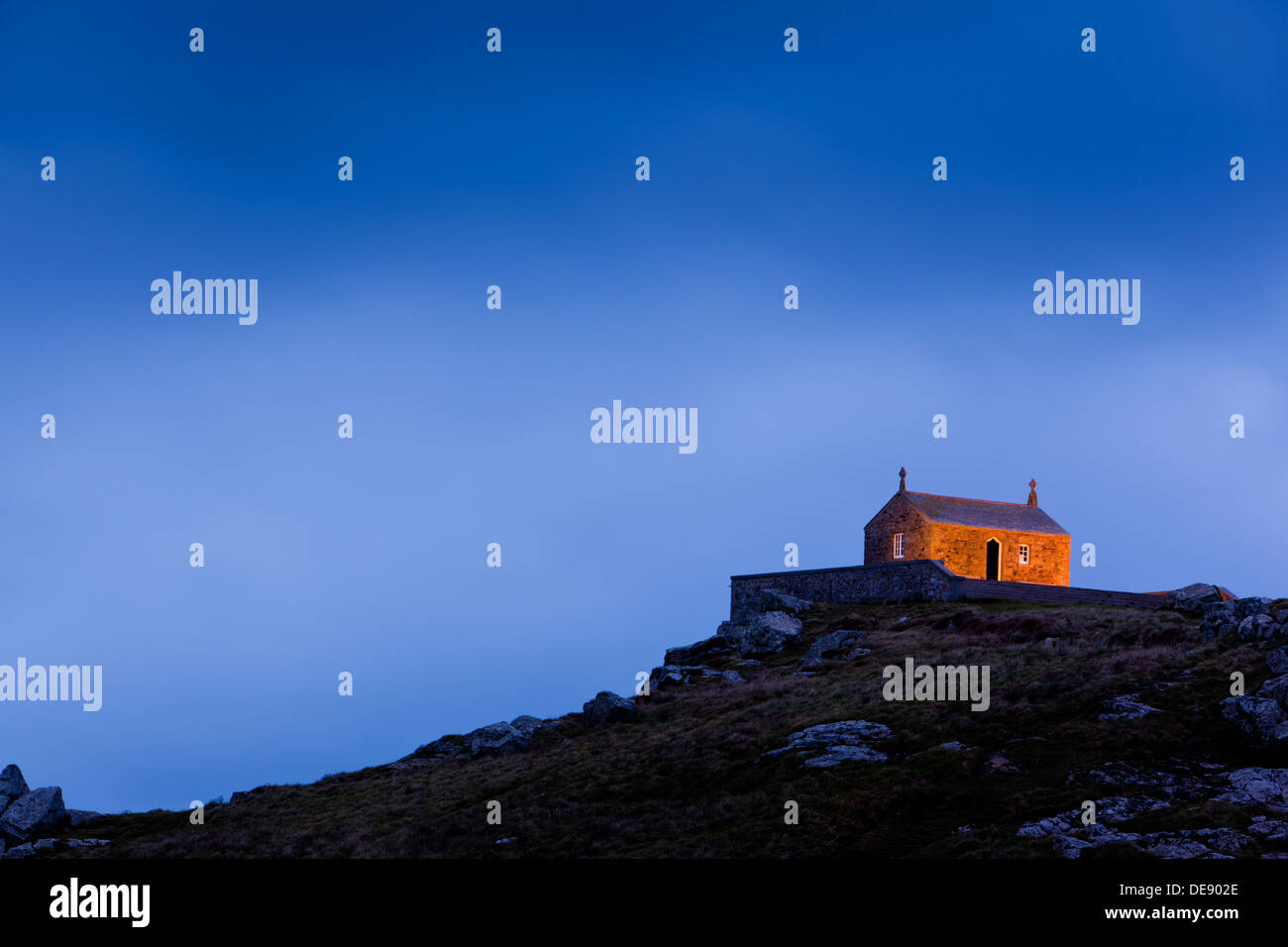 Old stone building on top of a rocky hill at night. - Stock Image