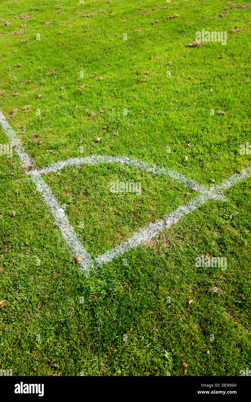 Close-up of the corner markings on a grassy football pitch. - Stock Image