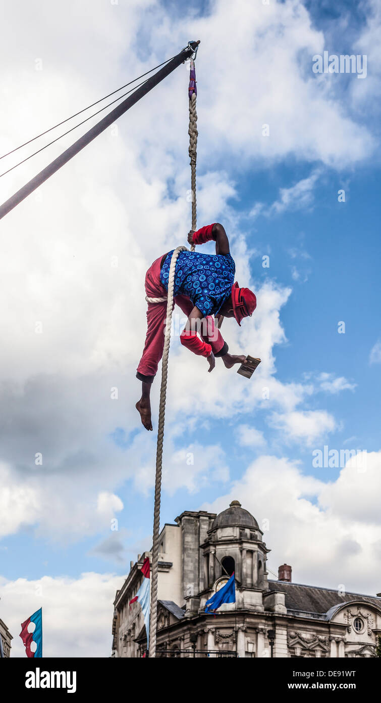 Acrobat from No Fit State Circus group reading a book suspended from a rope. 4SquaresWeekender festival, Birmingham. - Stock Image