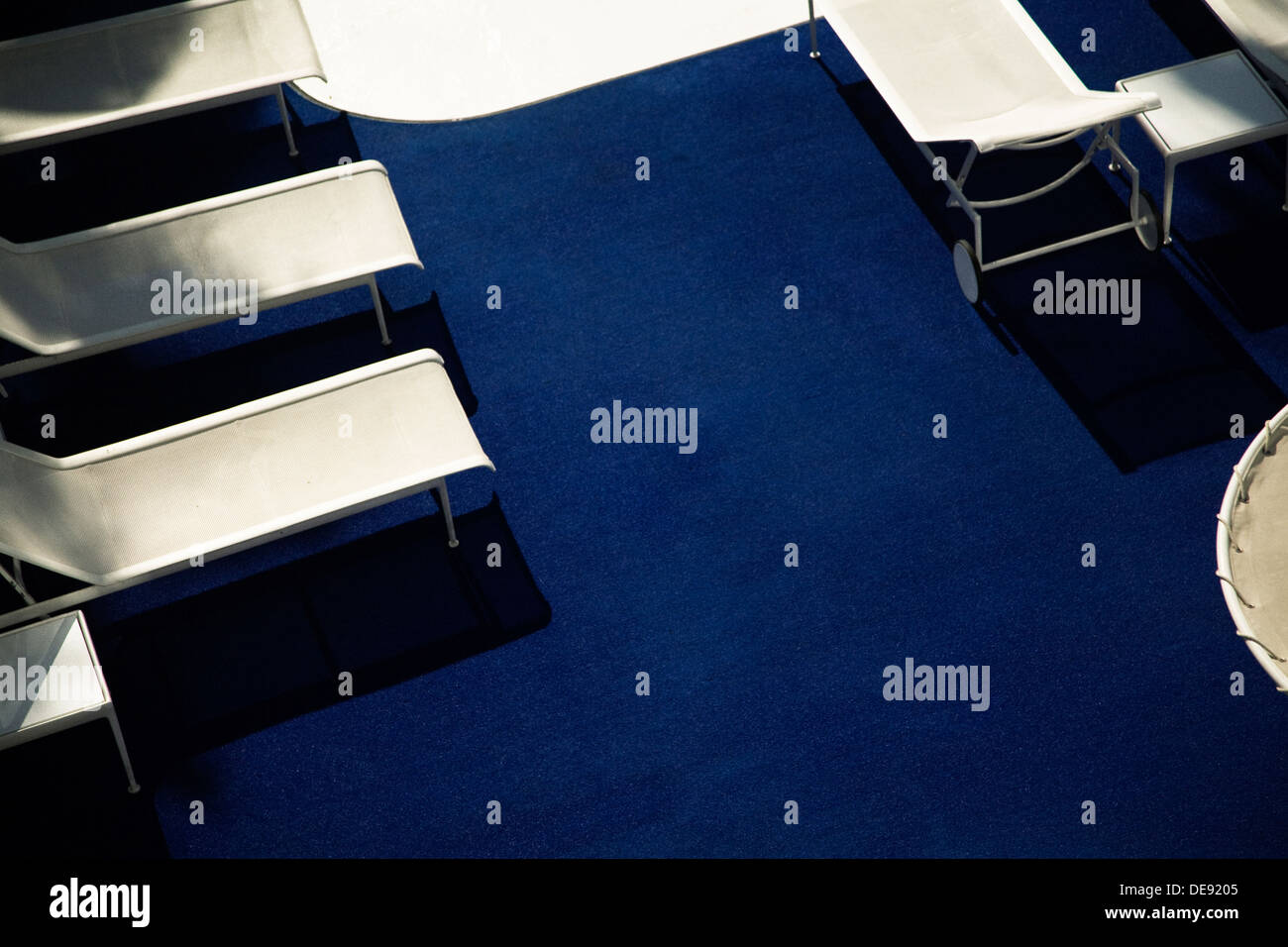 White Lounge Chairs Against Blue Carpet, High Angle View - Stock Image