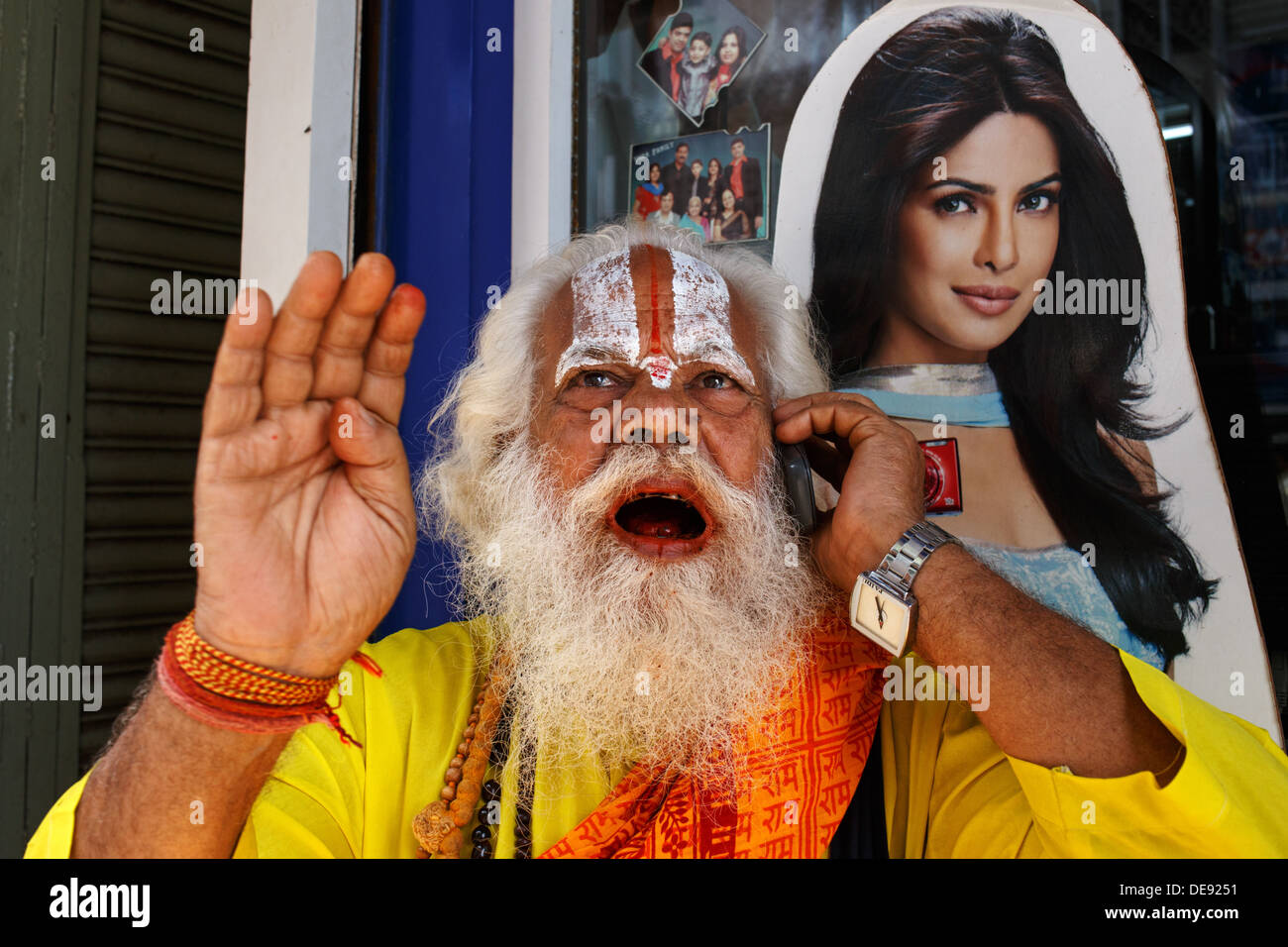 A Hindu priest speaks on a mobile phone (cellphone) in Central Mumbai, India with a poster advertising digital cameras - Stock Image