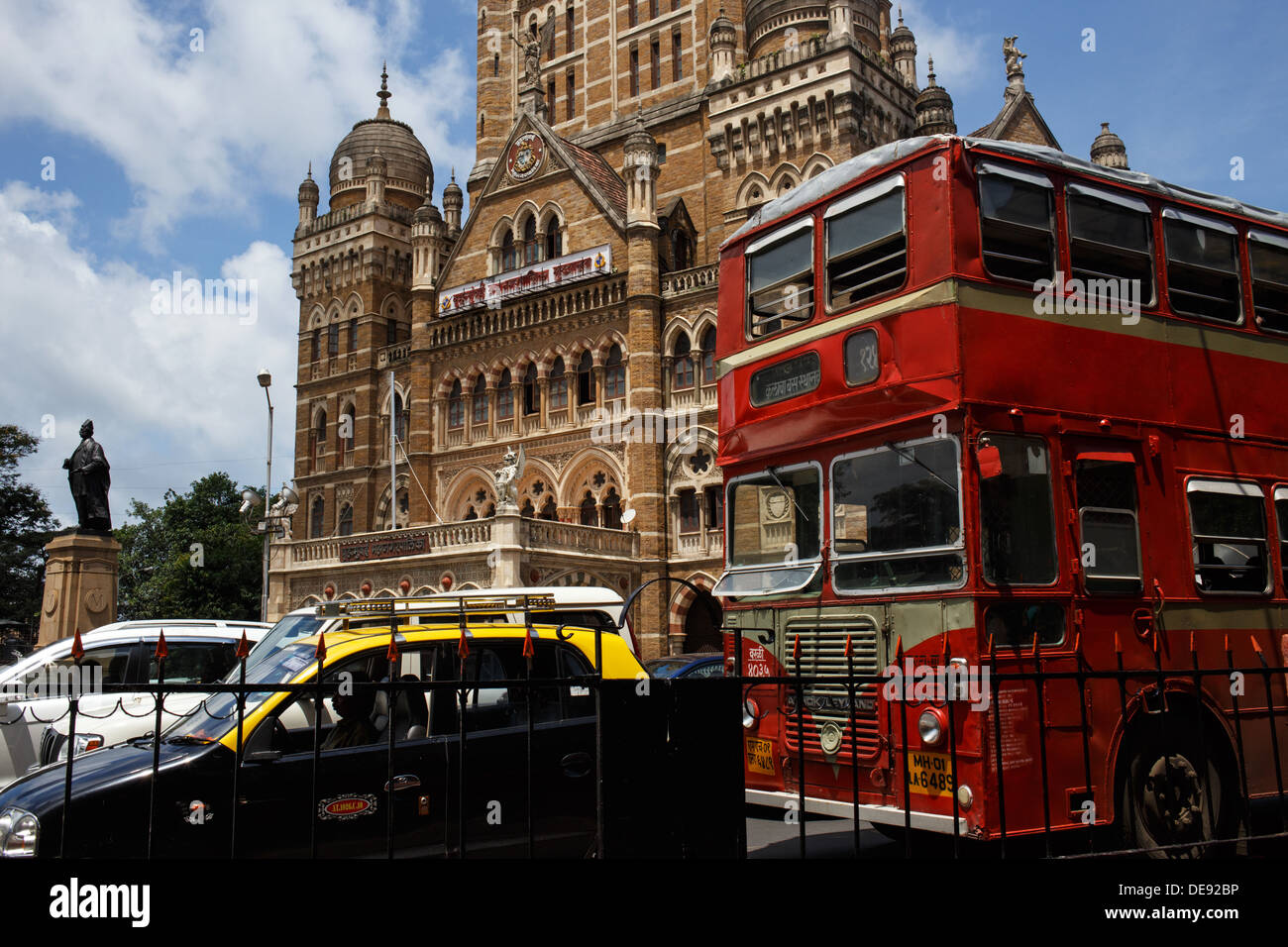 A red double decker bus, black taxi and cars in the traffic with the  Municipal Corporation Building in the background, Mumbai - Stock Image