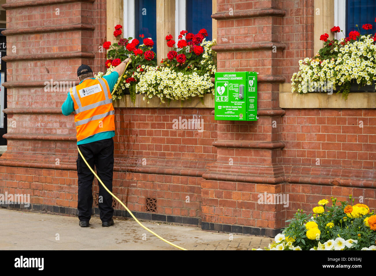 A council worker watering flowers of the Town Hall in Royal Leamington Spa, Warwickshire. Also includes a public defibrillator. - Stock Image