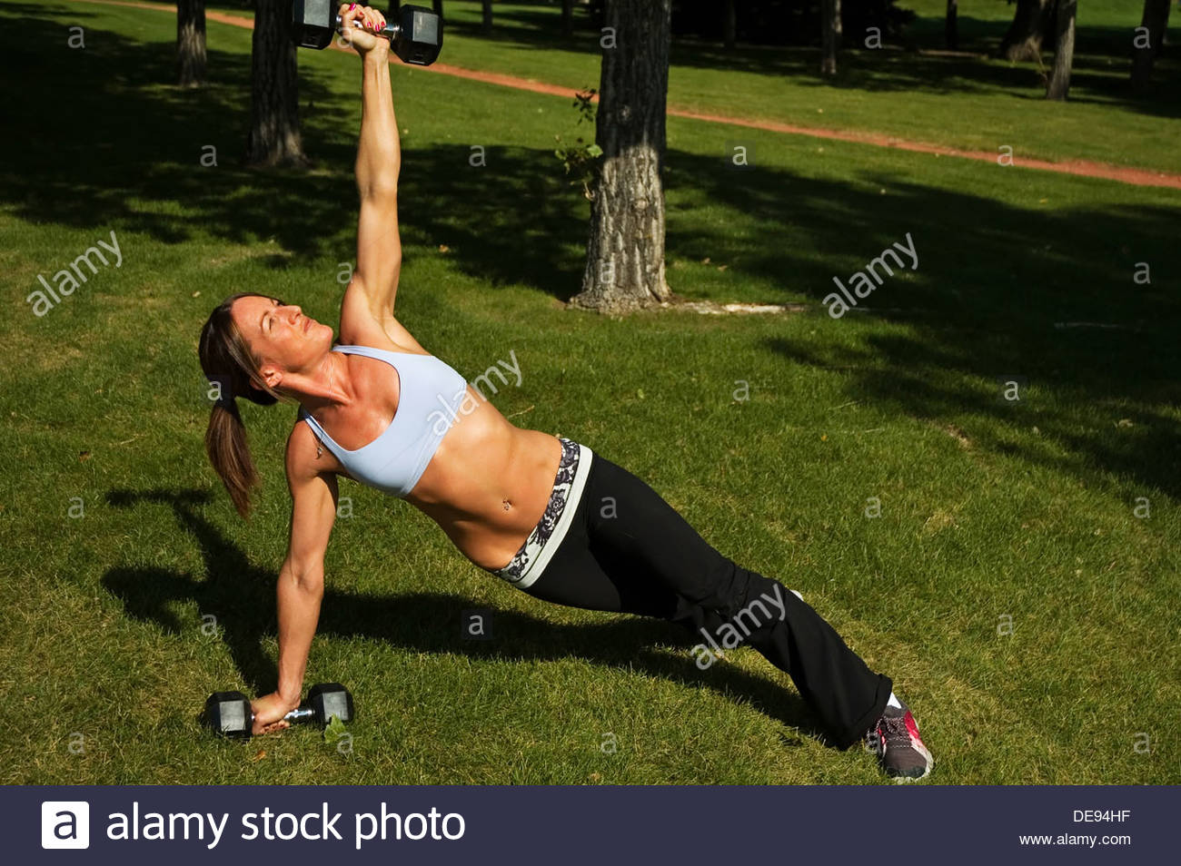 Woman doing a side plank twist with weights at a park. - Stock Image