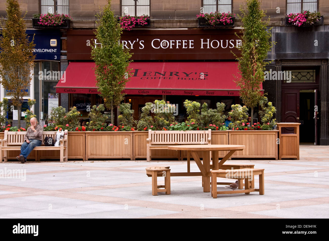 Man sitting eating outside at the City Square while people enjoying refreshments inside the Henry`s Coffee House in Dundee, UK - Stock Image