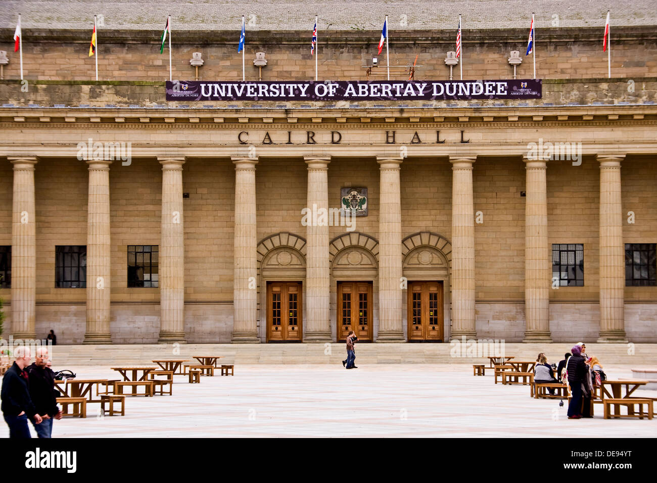 View of the Caird Hall Doric Columns and main entrance with several people relaxing around the City Square in Dundee, Stock Photo