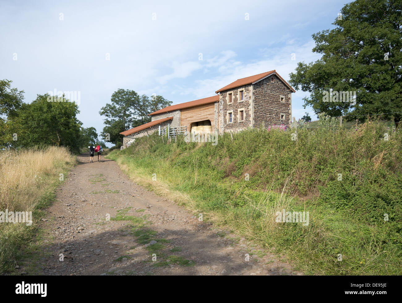 Pilgrims walking past farmhouse on the GR65 walking route the Way of St James in France - Stock Image