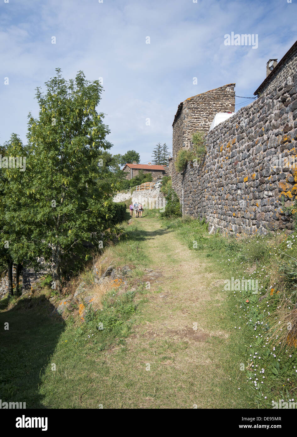 Pilgrims walking into the small French village of La Roche on the GR65 the Way of St James in France - Stock Image