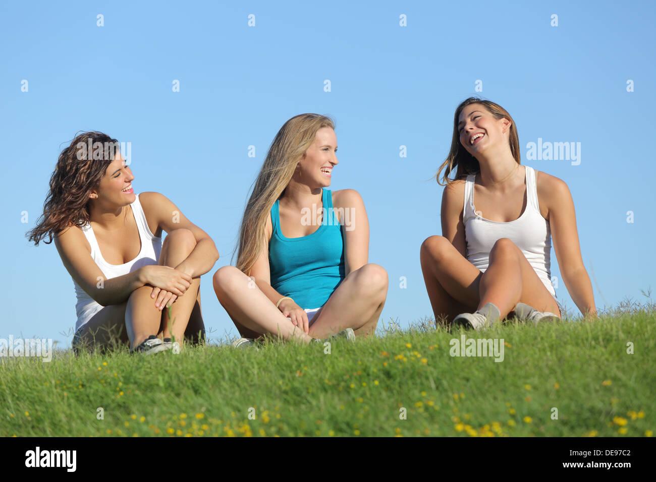 Three teenage girls converse outdoors on a California
