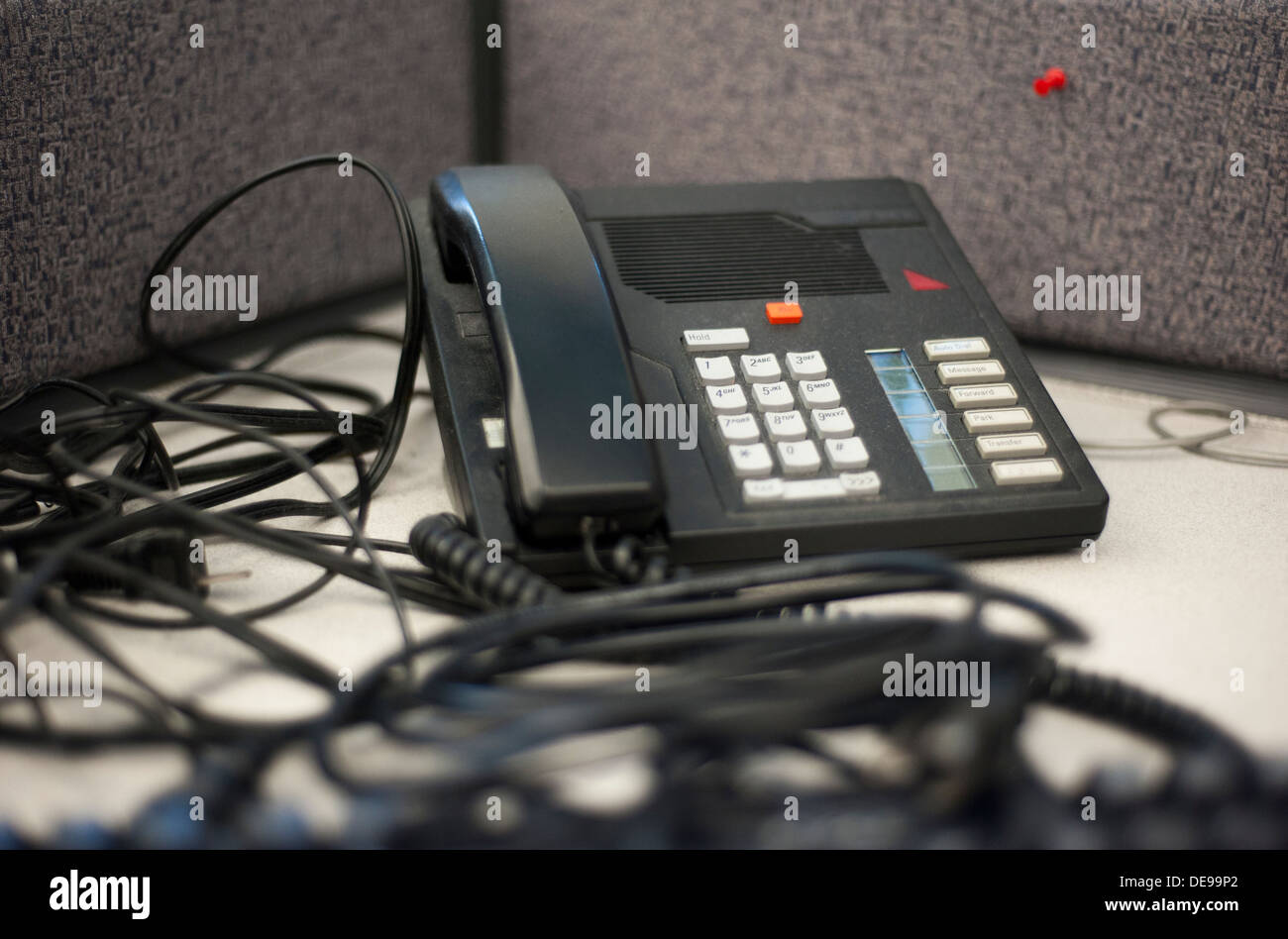 Dusty phone with tangled wires in an abandoned work space - Stock Image