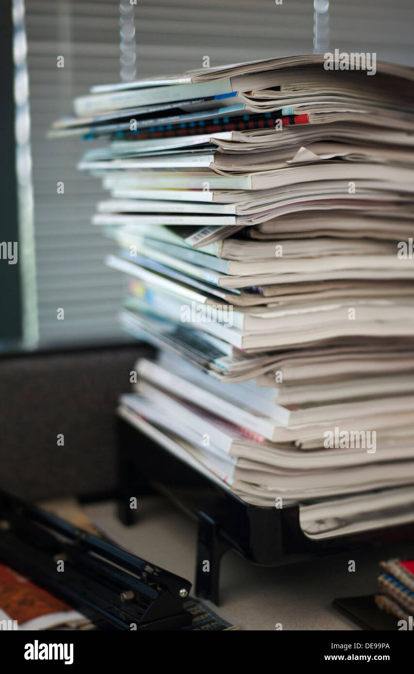 Overflowing inbox with excessive paperwork and magazines piled up - Stock Image