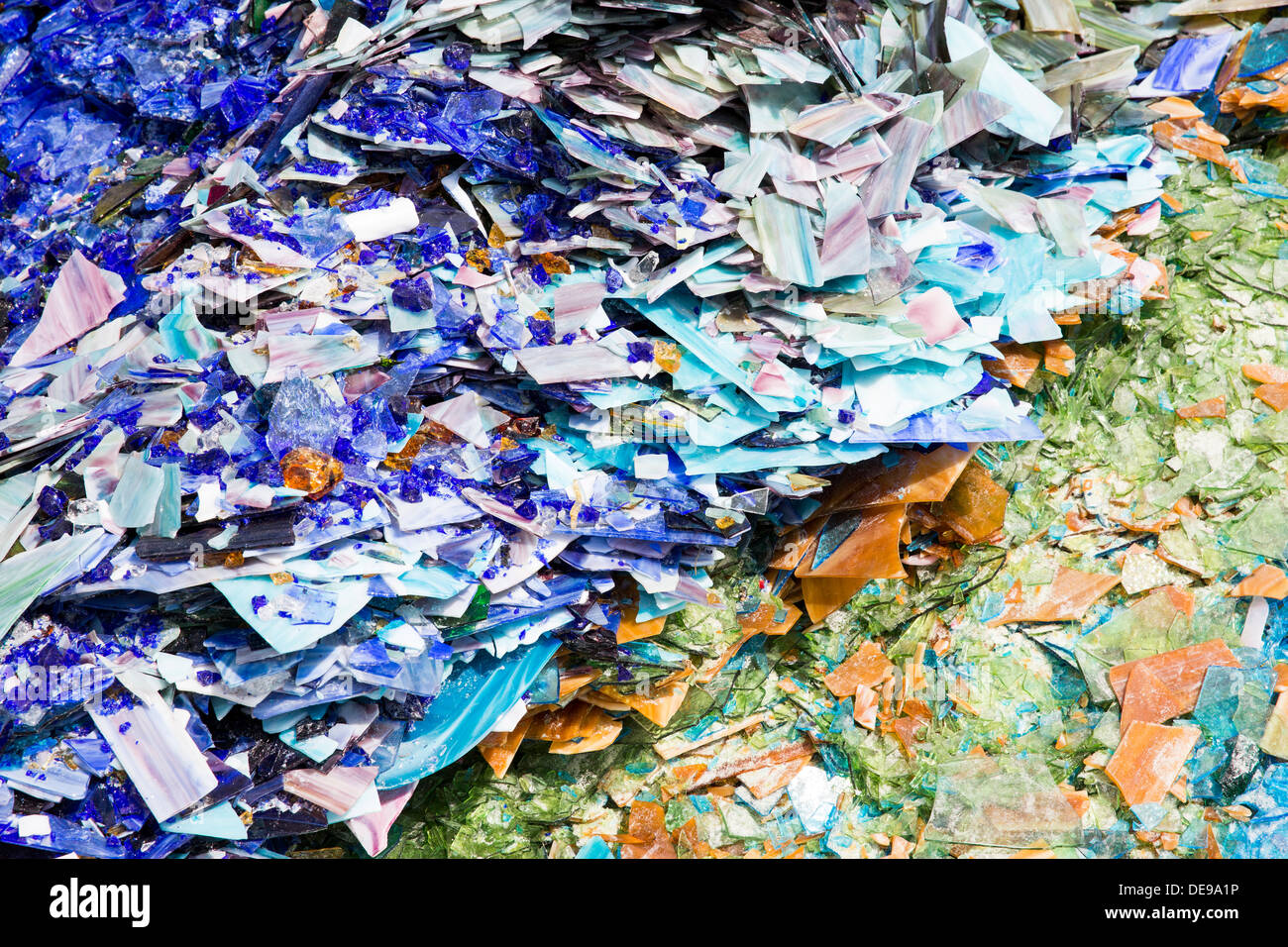 A scrap glass yard including stained glass and marbles. - Stock Image