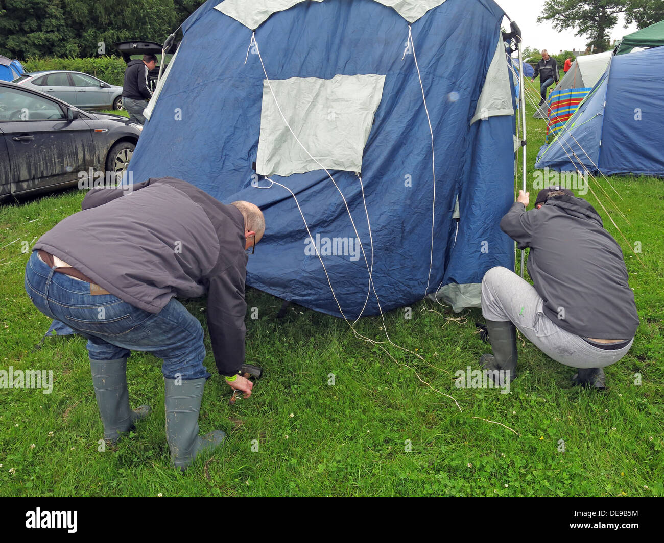 Happy campers erecting a tent at a festival or sporting event (F1 Grand Prix) - Stock Image