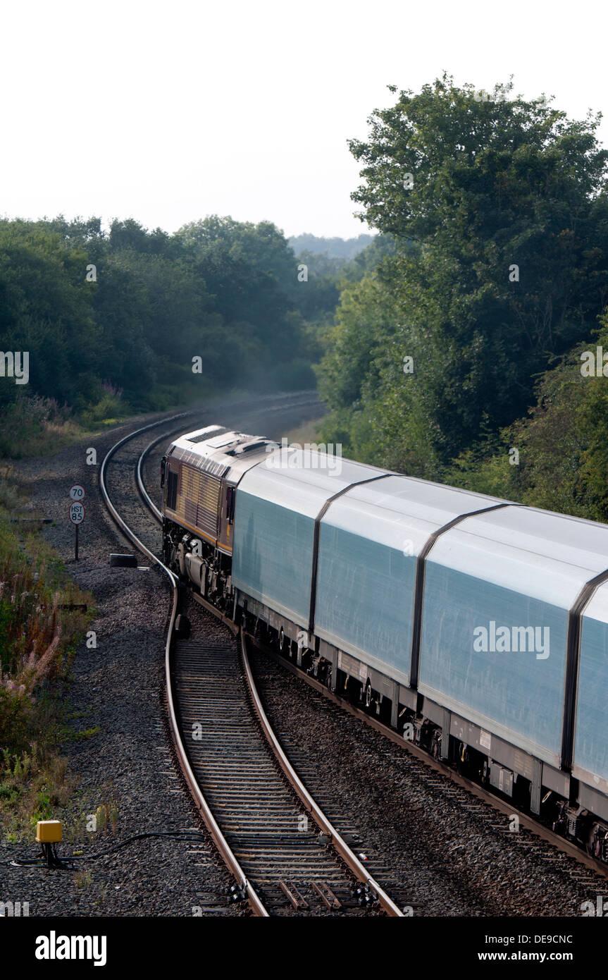 Class 66 diesel locomotive pulling a covered car train, Hatton, Warwickshire, UK - Stock Image