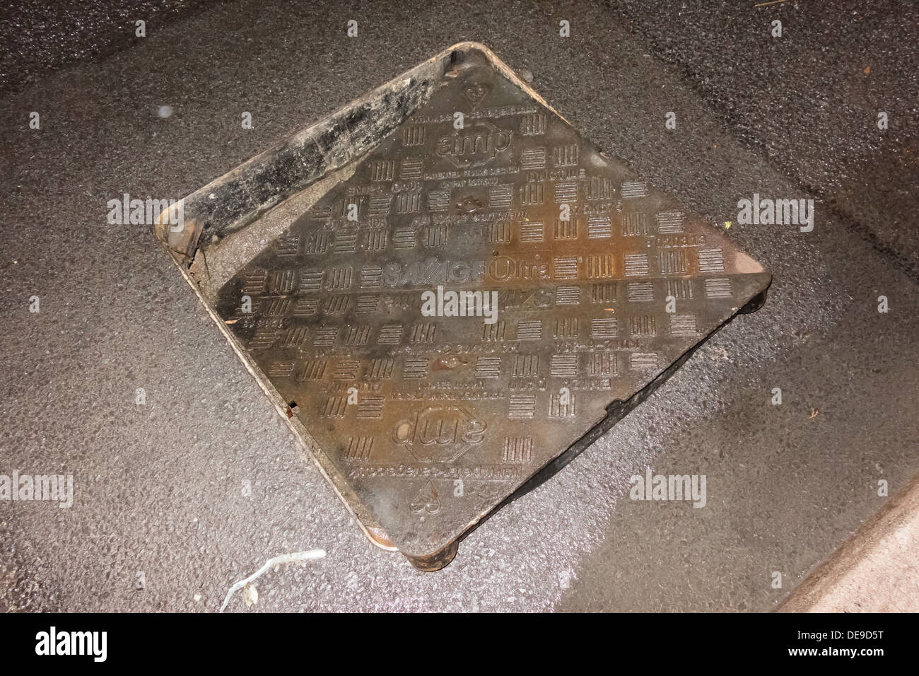 Sewer manhole cover displaced by flooding from underneath leaving a hazard to drivers or cyclists - Stock Image