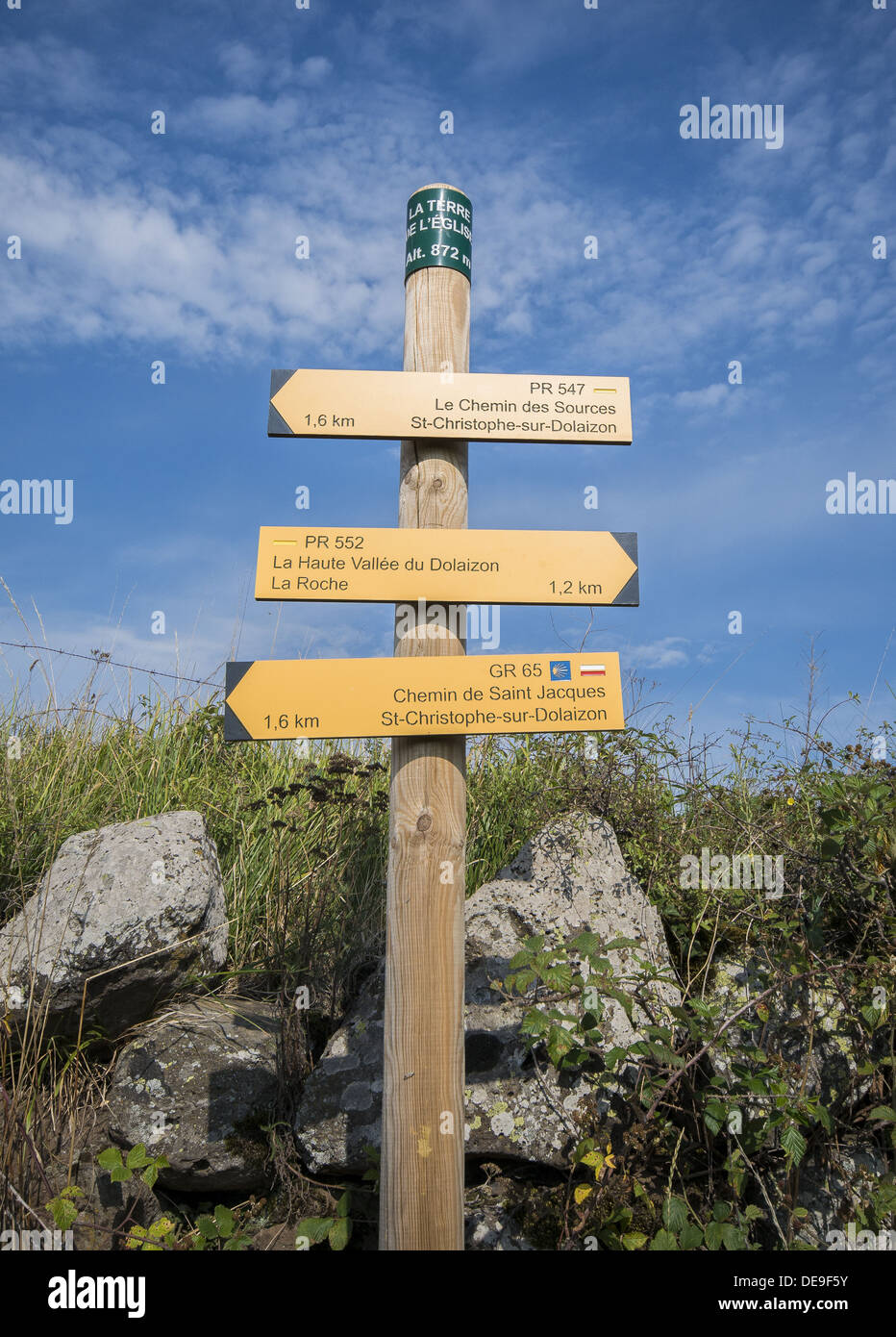 Yellow waymarker signpost on the GR65 walking route the Way of St James in the Auvergne region of France - Stock Image