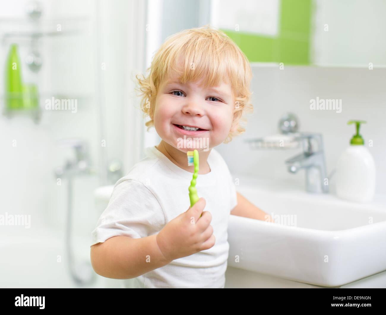 Happy kid or child brushing teeth in bathroom. Dental hygiene. Stock Photo