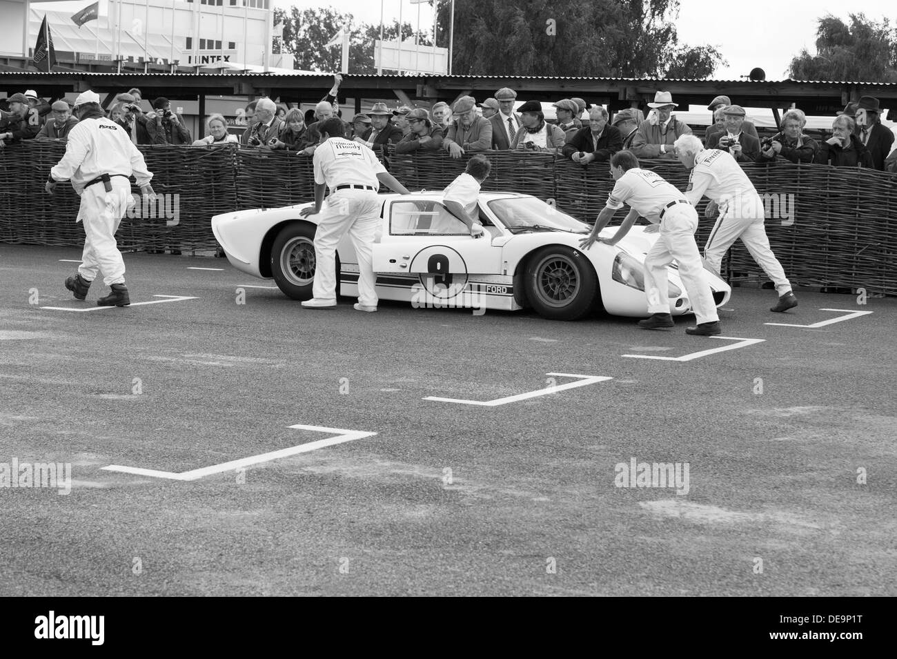 racing team pushing a Ford GT 40  onto a dummy grid at the 2013 goodwood revival vintage weekend   ( editorial use only ) mono - Stock Image