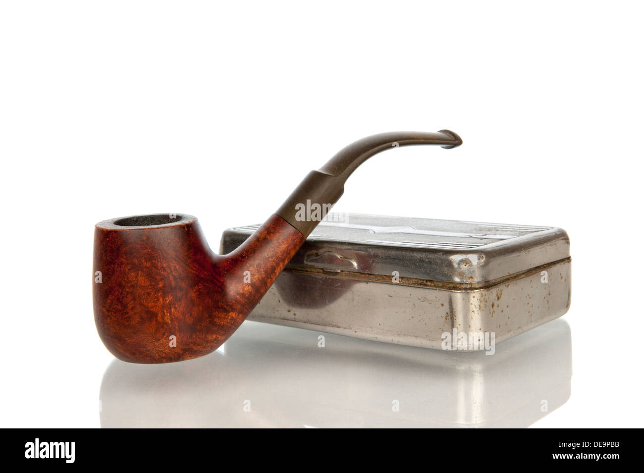 Antique brown pipe with iron tobacco box in closeup and isolated in white - Stock Image