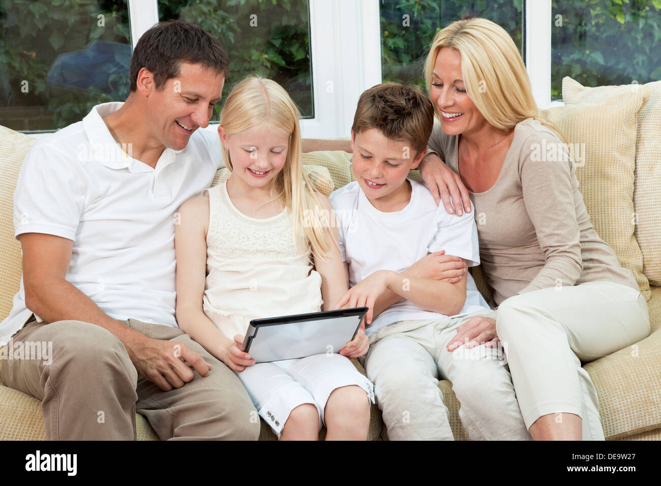 An attractive happy, family of mother, father, son and daughter sitting on a sofa at home having fun using a tablet computer - Stock Image