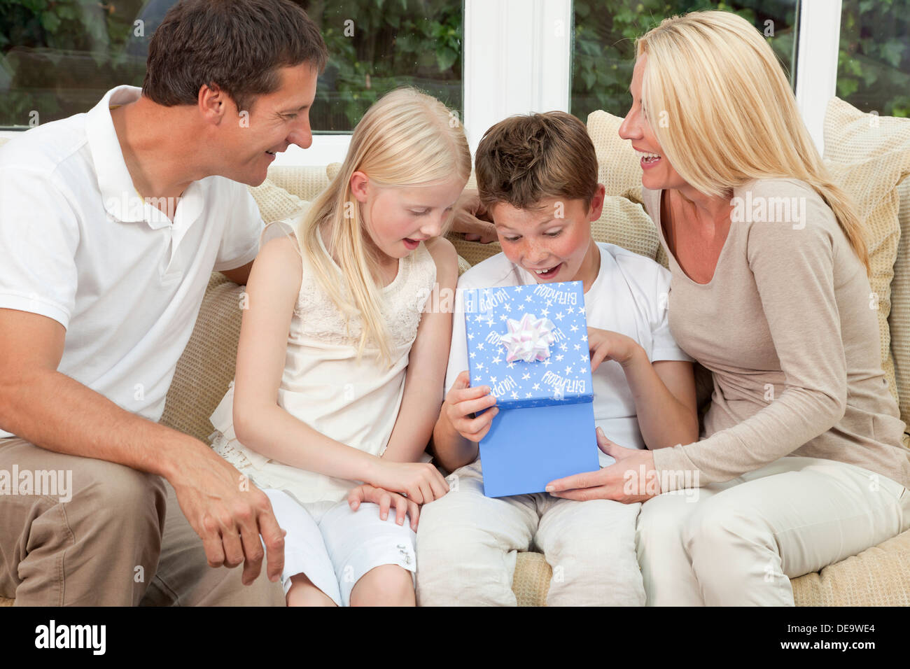 happy family mother father son and daughter sitting on a sofa at home the boy child is opening a birthday present in a blue box - Stock Image