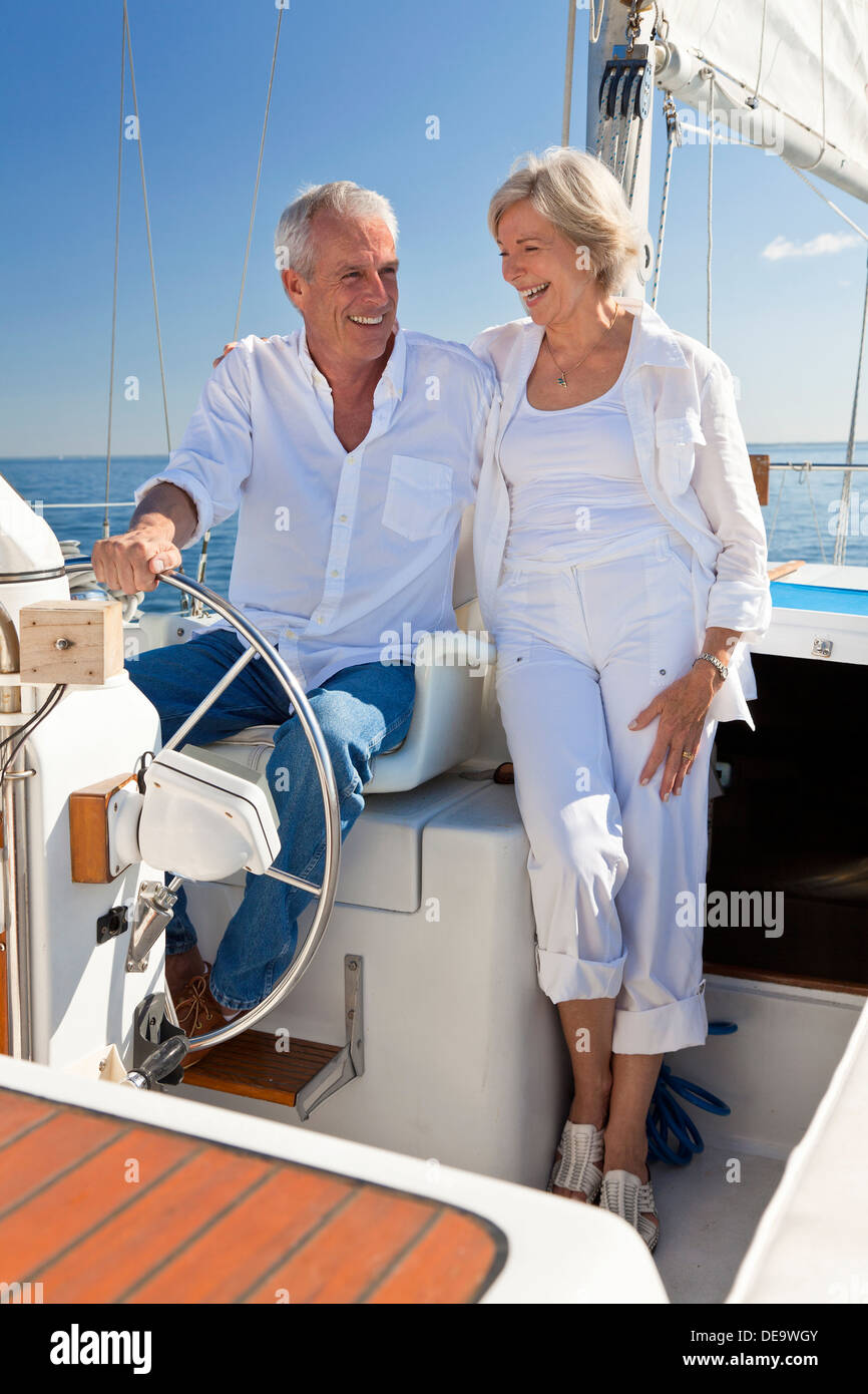 A happy senior couple sitting at the wheel of a sail boat on a calm blue sea - Stock Image