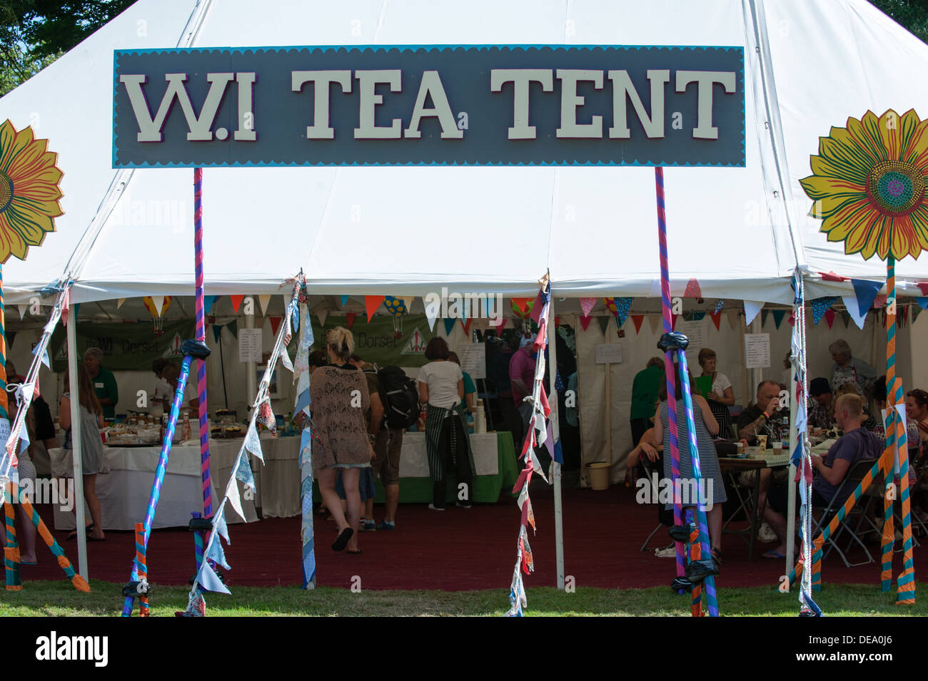 Women's Institute W.I tea tent with a large sign, colourful bunting and people inside at the music festival Camp Bestival - Stock Image
