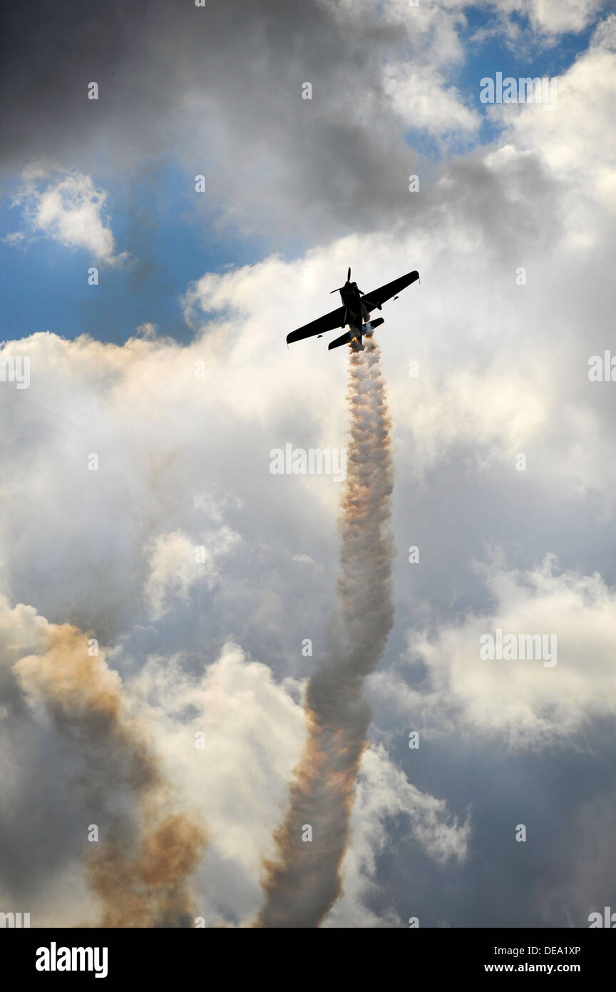 an aerobatic plane with smoke trail silhouetted against clouds and sky - Stock Image