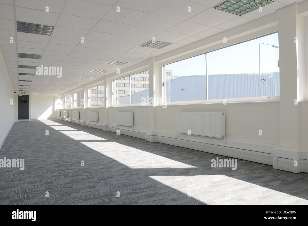 An Interior Of And Empty Modern Office Space With Grey Carpet And White  Walls, Looking Out The Windows