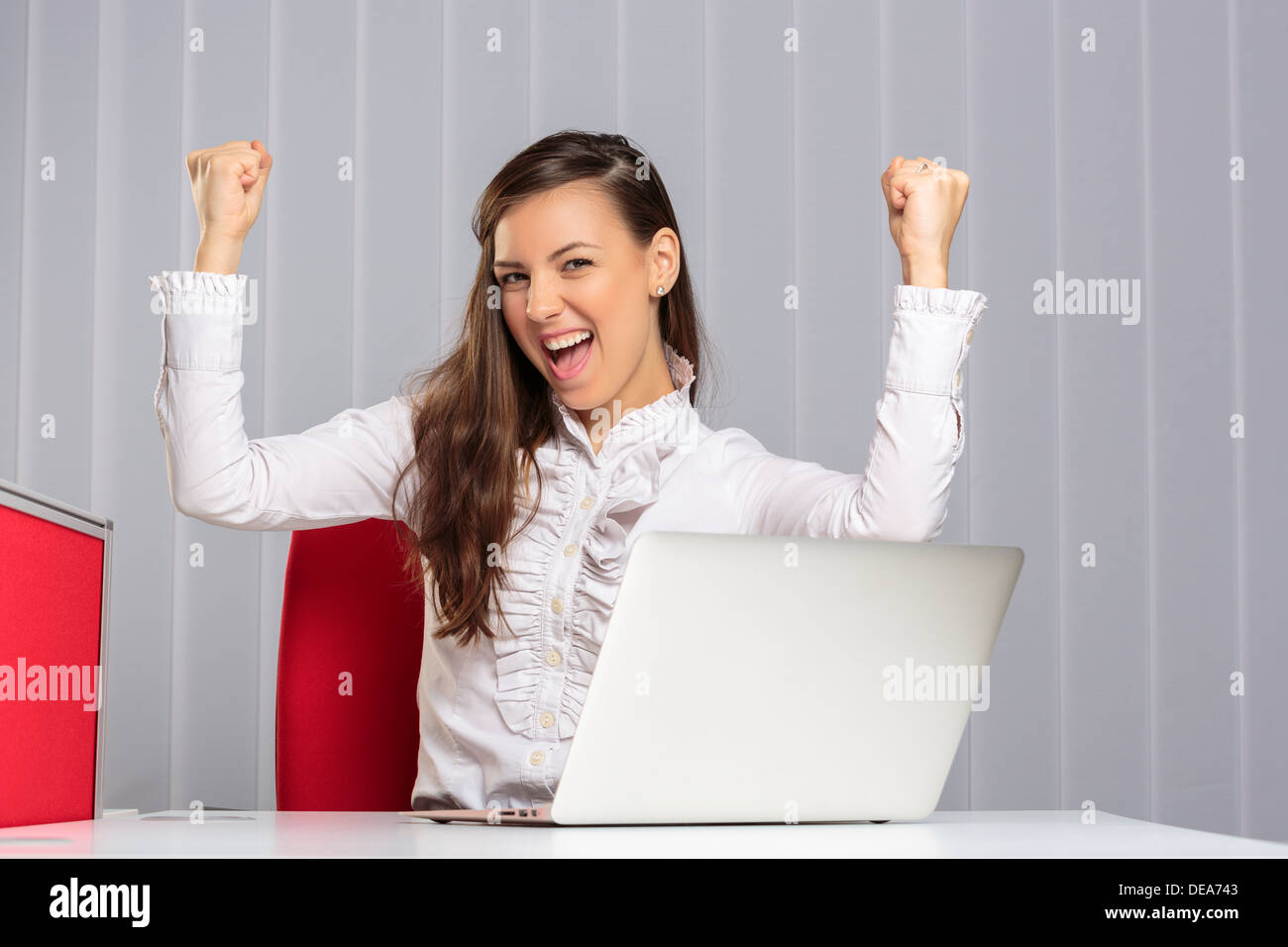 Excited female executive screaming and celebrating with raised clenched fists her business victory in the office. - Stock Image
