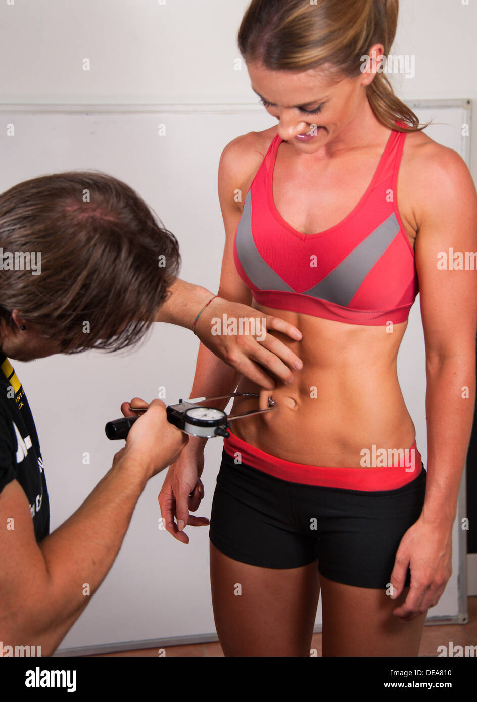 Toned woman having body fat measured with callipers - Stock Image