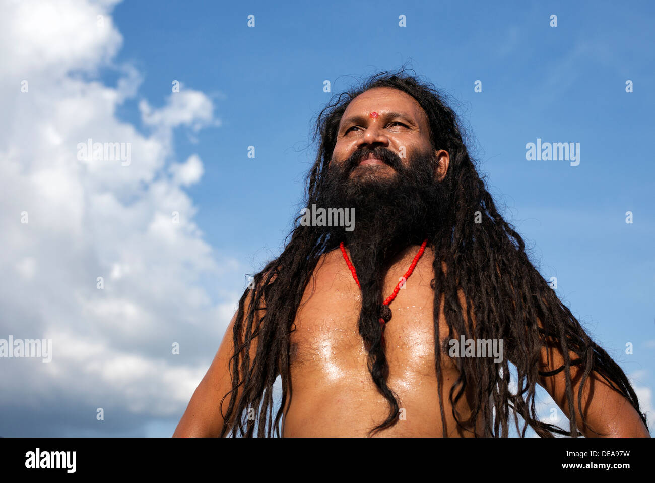 Indian Sadhu with dreadlocks against a blue cloudy sky. India - Stock Image