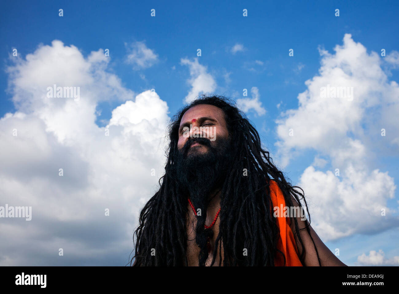 Indian Sadhu in meditation against a blue cloudy sky. India - Stock Image