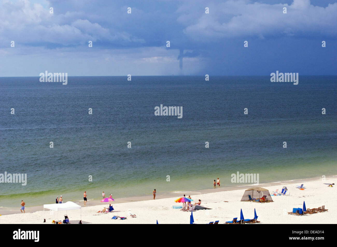 water cyclone forming in the Atlantic ocean with people on beach watching Stock Photo