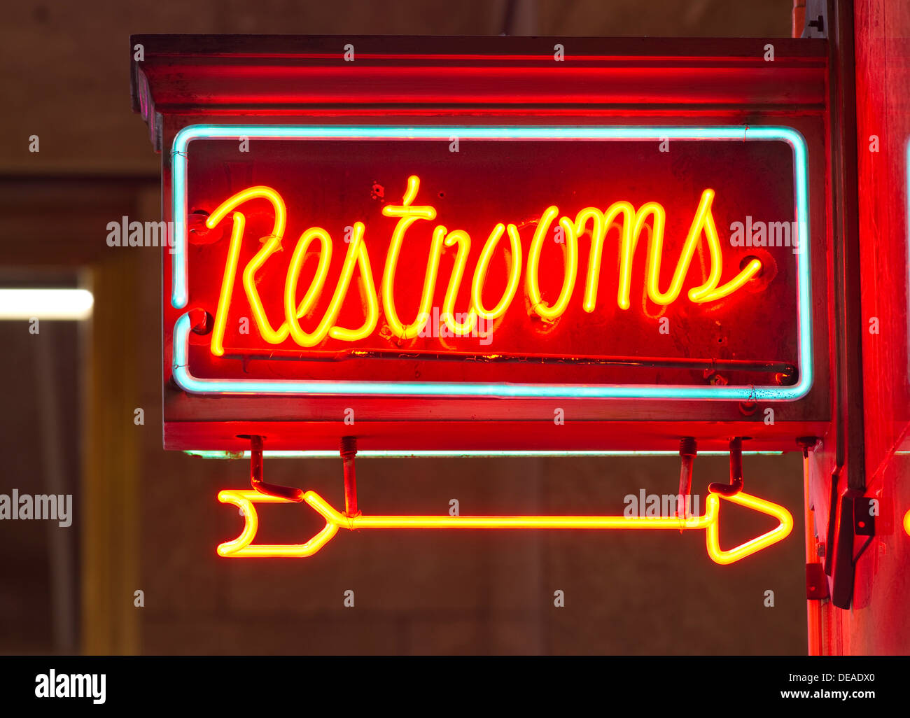 A red neon sign points the way to the restrooms - Stock Image