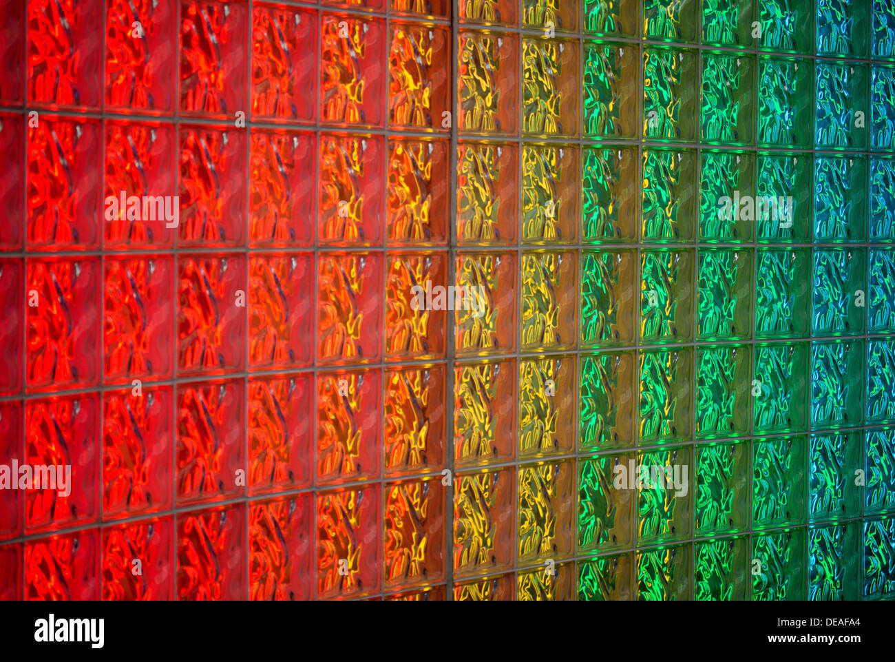Detail of glass block wall back-lit with neon lights in rainbow colors. Image shows detail of blocks and colors. - Stock Image