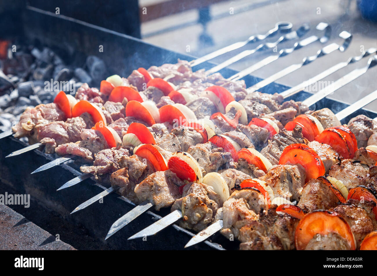 Juicy slices of meat with sauce prepare on coals - Stock Image