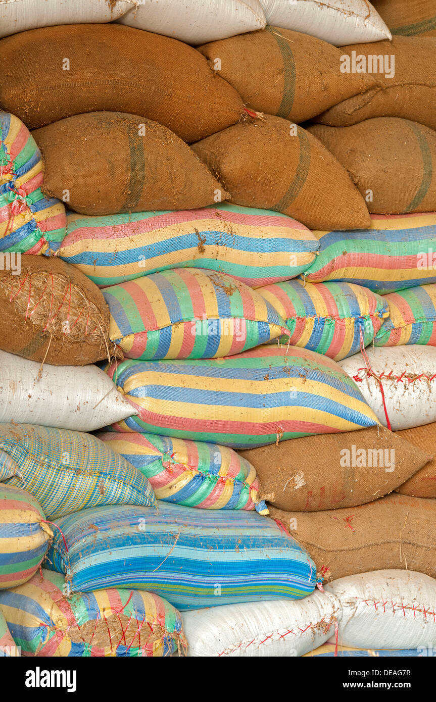 Plump bags of rice stacked in a rice warehouse, Battambang, Cambodia, Southeast Asia, Asia - Stock Image