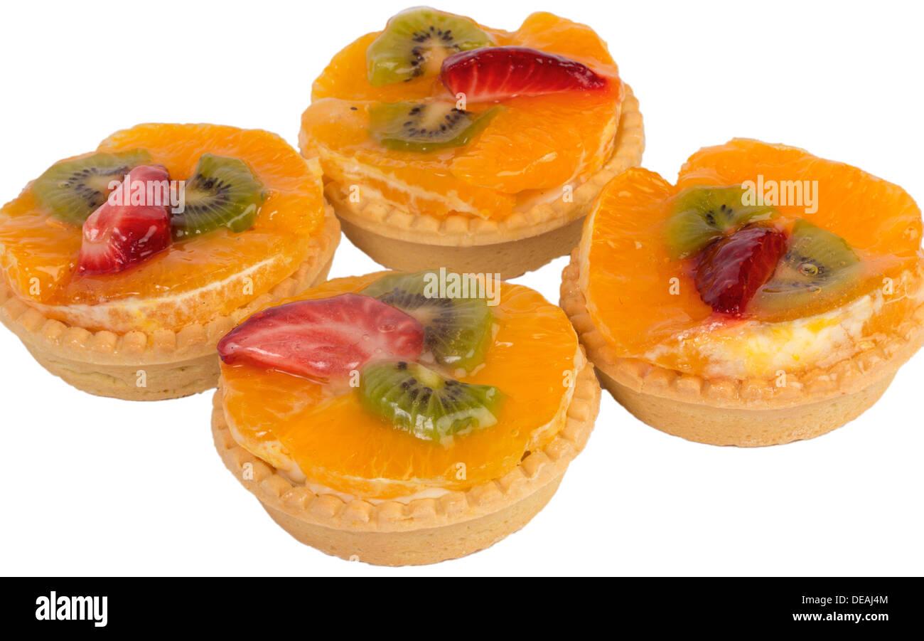 Four tarts with orange, kiwi and strawberry isolated on white - Stock Image