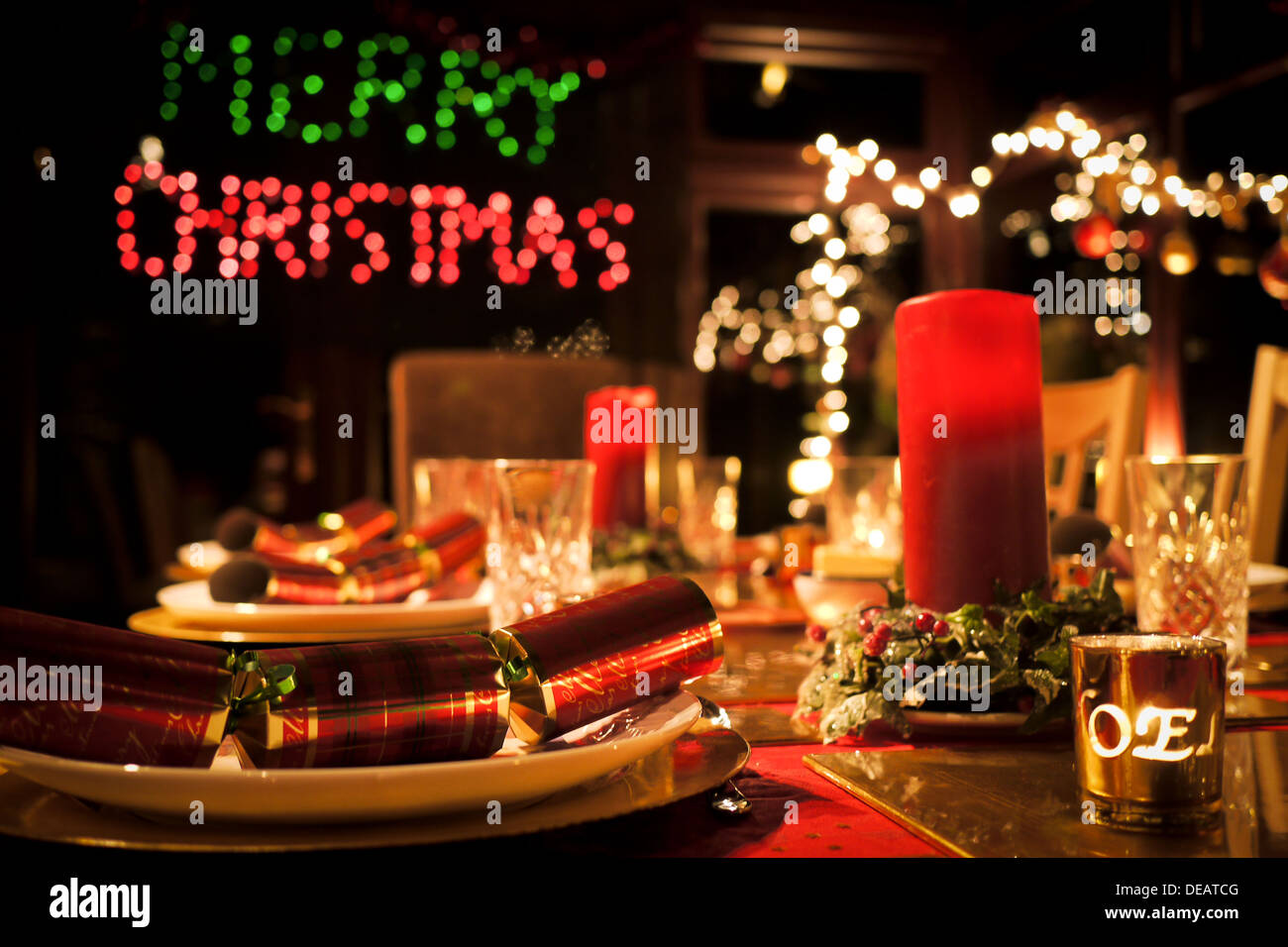 Fully laid Christmas table with candles and Merry Christmas in lights blurred in the background - Stock Image