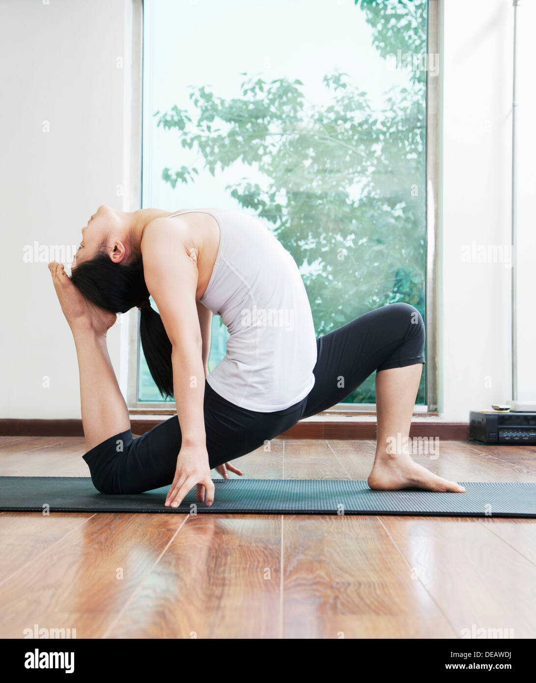 Woman bent over backwards in a yoga position in a yoga studio, side view - Stock Image
