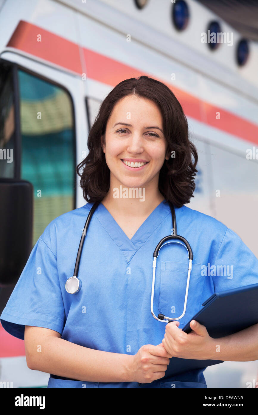 Portrait of smiling female paramedic in front of am ambulance - Stock Image