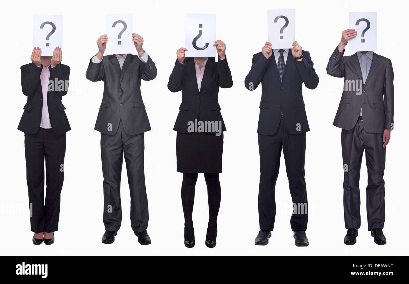 Five business people holding up paper with question mark, obscured face, studio shot - Stock Image