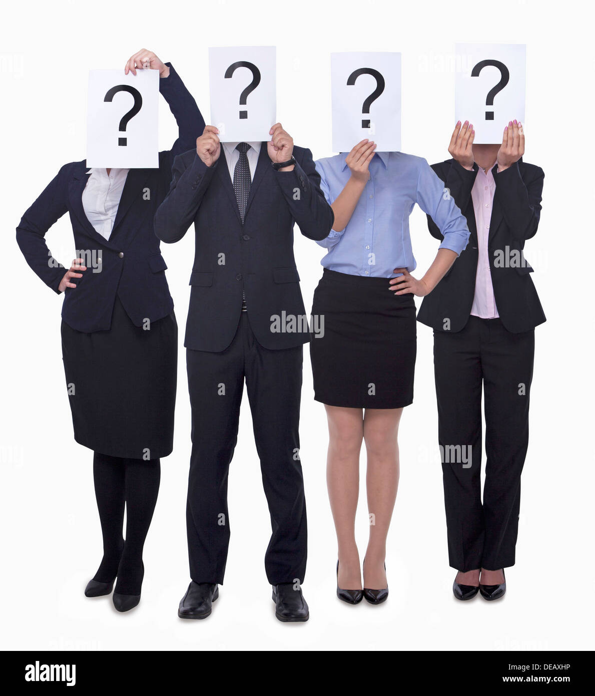 Four business people holding up paper with question mark, obscured face, studio shot - Stock Image