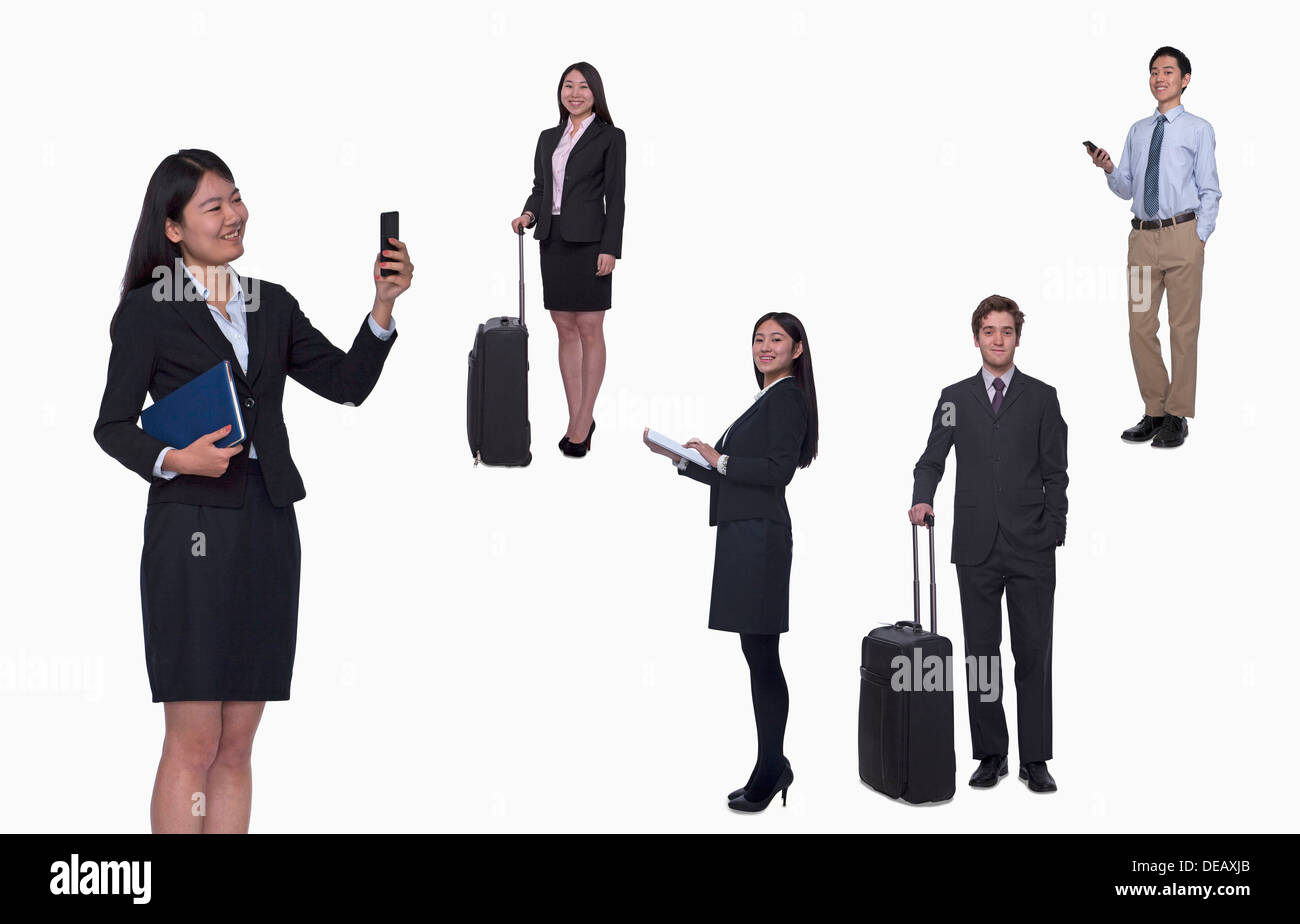 Group of business people working, taking photos, texting, studio shot, full length - Stock Image