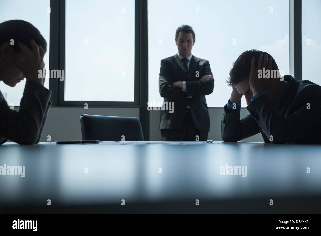 Three frustrated and overworked business people in the board room with arms crossed and head in hands. - Stock Image