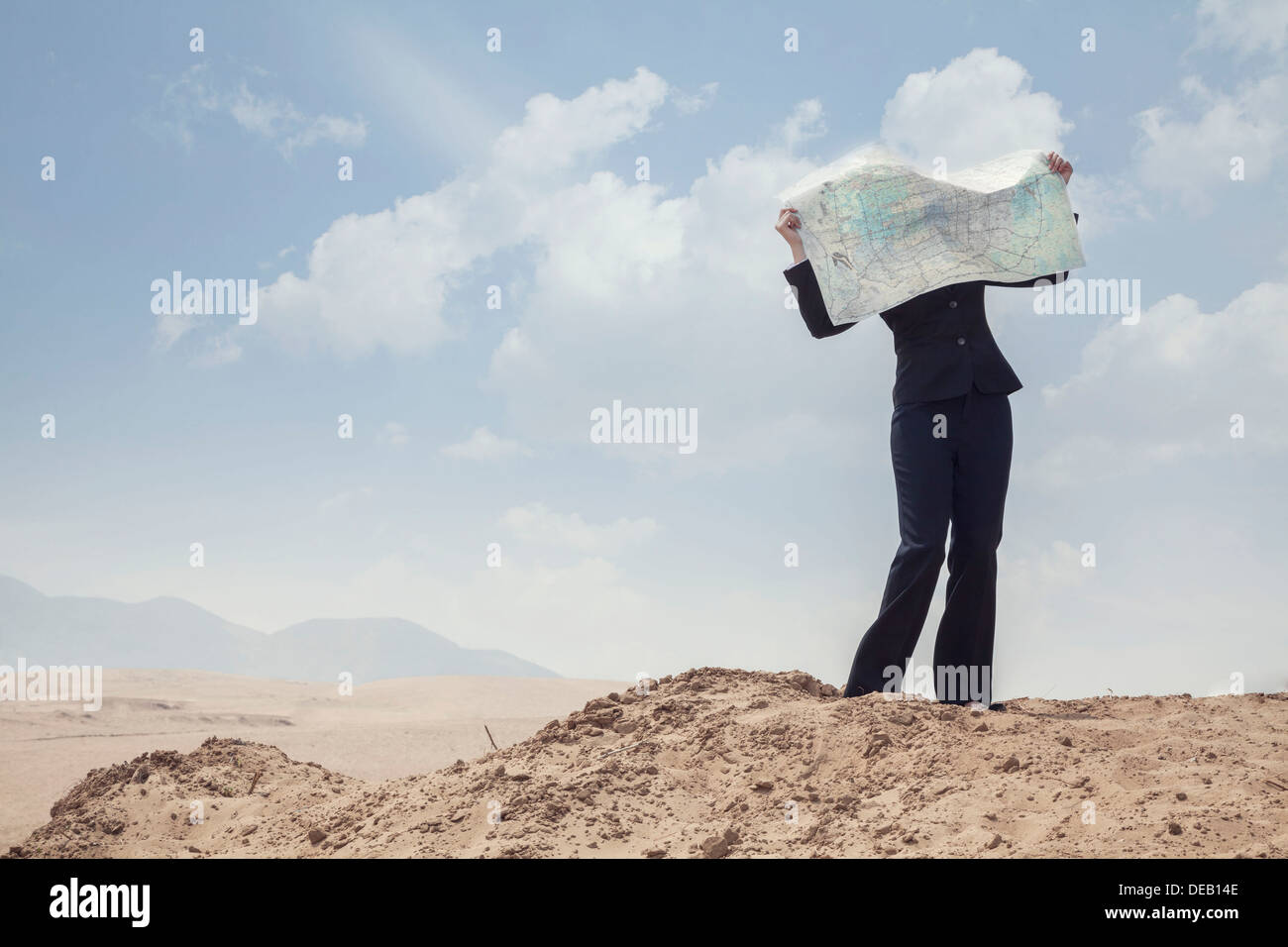 Young Businesswoman looking at a map in the middle of the desert - Stock Image