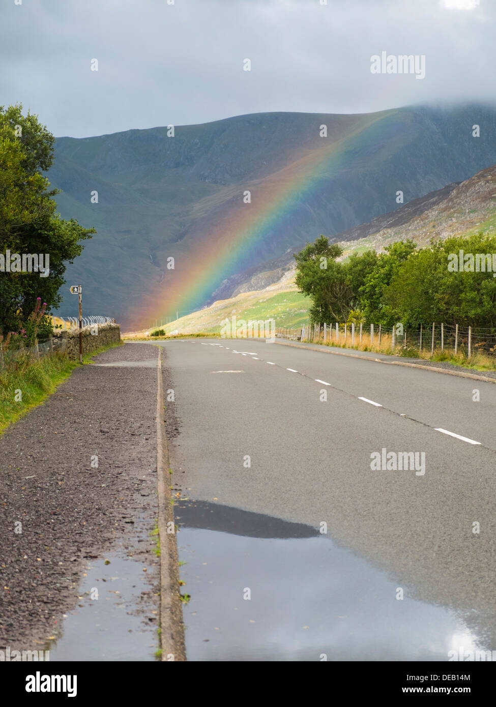 View along Thomas Telford's A5 road to end of a rainbow with sunshine in Ogwen valley following rain In Snowdonia National Park Conwy Wales UK Britain - Stock Image