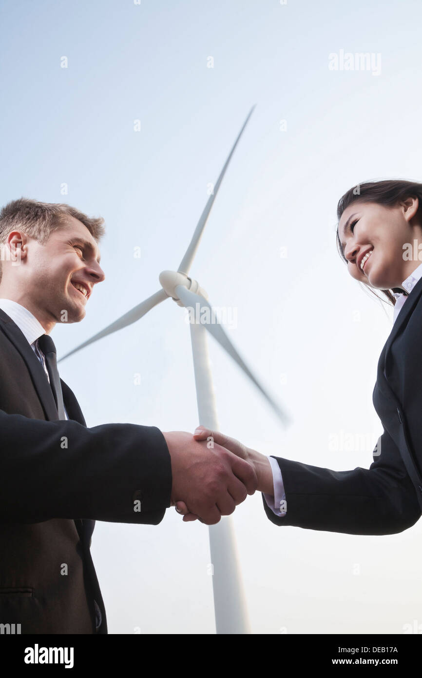 Two smiling young business people shaking hands in front of a wind turbine - Stock Image
