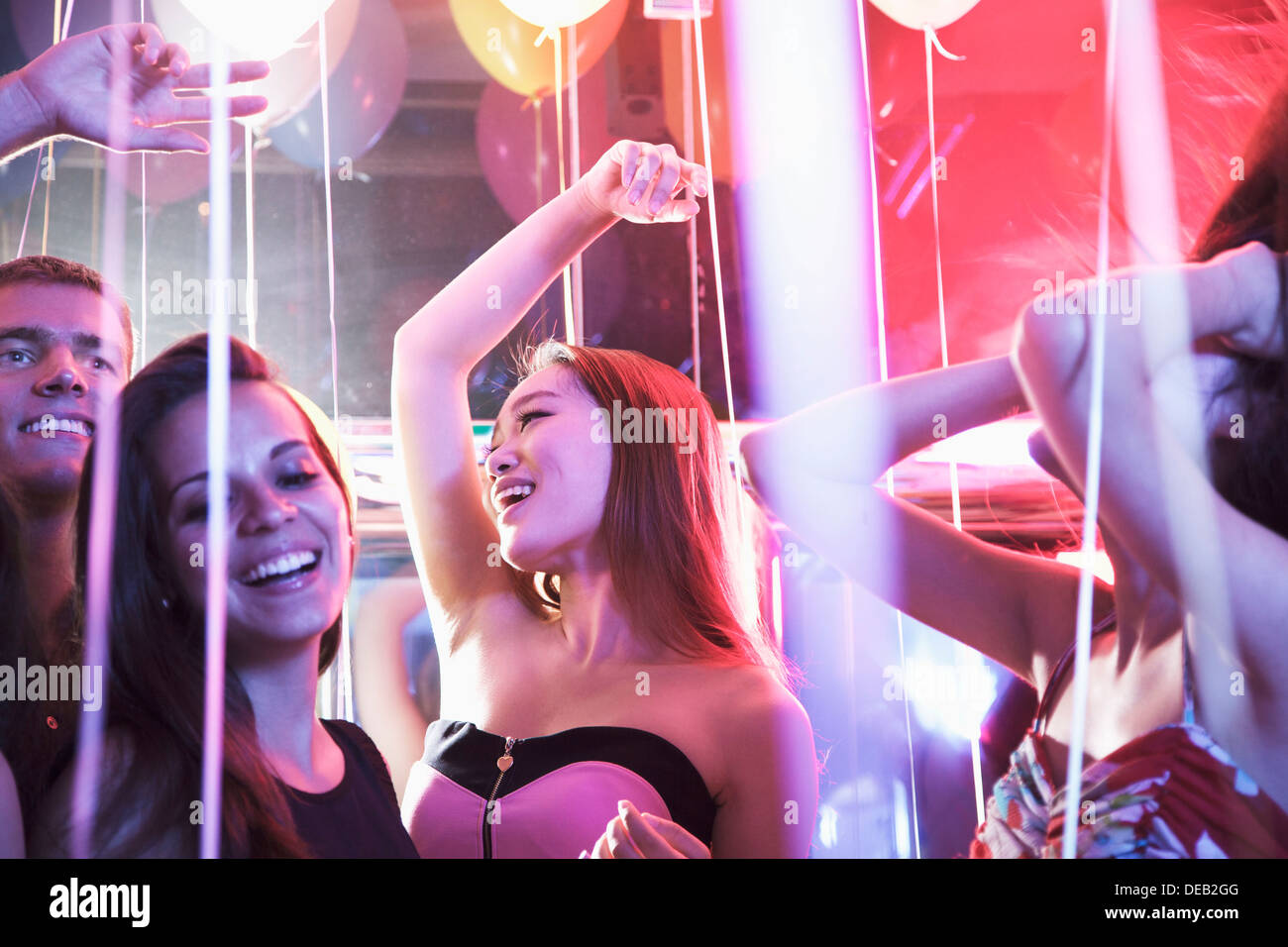 Multi-ethnic group of friends with hands in the air dancing among balloons in a nightclub - Stock Image